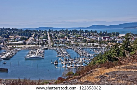 This is an aerial landscape of Anacortes Washington, overlooking the marina.  Puget Sound and the San Juan Islands are in the distance. Small coastal town in Skagit County, Washington state. - stock photo