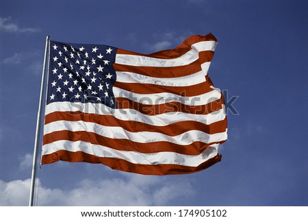 This is an American flag, waving in the wind. It is on a flagpole set against a blue sky with white puffy clouds. - stock photo