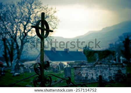This is an artistically toned image with focus on Irish cemetery crucifix.  Ireland landscape and graveyard seen in the background. - stock photo
