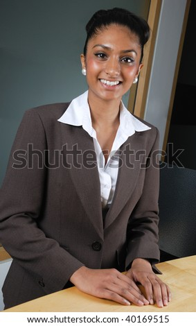 This is an image of a business woman smiling confidently at a reception desk.