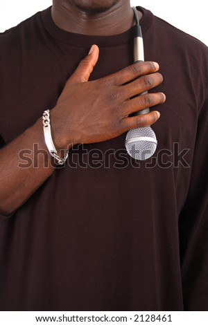 This is an image of man with his hand against a microphone to his chest. - stock photo
