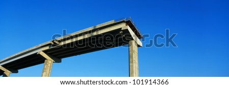 This is an unfinished freeway or dead end road. There is a huge drop-off where the road ends. It is supported by concrete pillars that traditionally hold up freeways. - stock photo