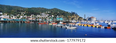 This is Avalon Harbor. There are various types of boats moored in the harbor. The famous casino building is to the far right with houses built into the hillside. - stock photo