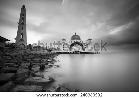 This is black and white image of Malacca Straits Mosque (Masjid Selat Melaka) . It is located at Malacca , Malaysia and also located in the Strait of Malacca, where it is a busy route in the world . - stock photo