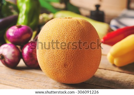 This is close up image of melon and various vegetables on wooden background