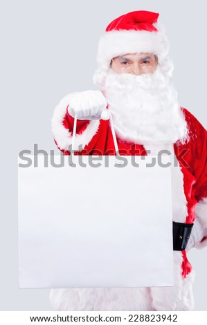 This is for you! Traditional Santa Claus stretching out hand with shopping bag while standing against grey background - stock photo