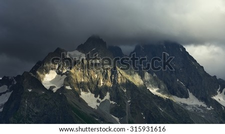 This is gloomy summits in Caucasus mountains in evening - stock photo