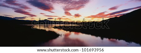 This is Lake Casitas at sunrise. There is a pinkish glow from the sun reflected in the lake. - stock photo