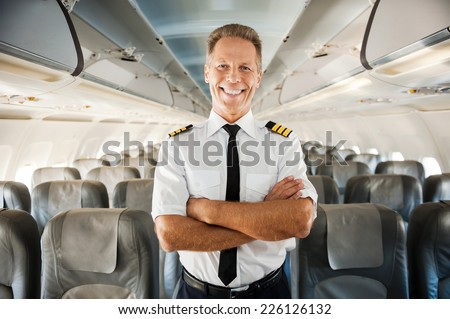 This is my plane. Confident male pilot in uniform keeping arms crossed and smiling while standing inside of the airplane - stock photo
