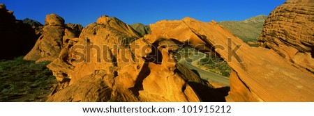 This is Nevada's first state park in red rock country. There is a sandstone arch that forms a window. It reveals a road that curves in a letter s shape. - stock photo