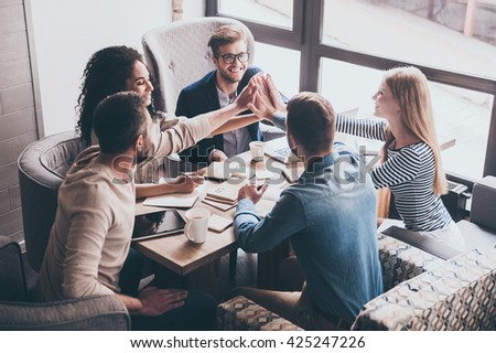 This is our success! Cheerful young people giving each other high-five with smile while sitting at the office table on business meeting - stock photo