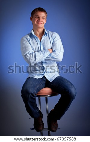 This is portrait of a young man sitting on bar chair - stock photo