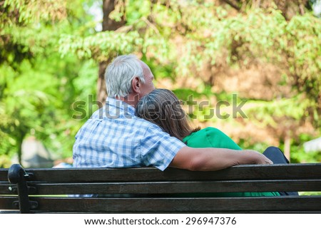This is rear view portrait image of senior couple in love, sitting on bench on sunny day, in summer. Woman is leaning on man's shoulder. Mas is hugging his wife. Selective focus. - stock photo