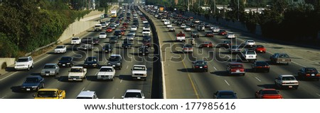 This is rush hour traffic on the 405 Freeway at sunset. There are 10 total lanes of traffic with cars traveling in both directions. - stock photo