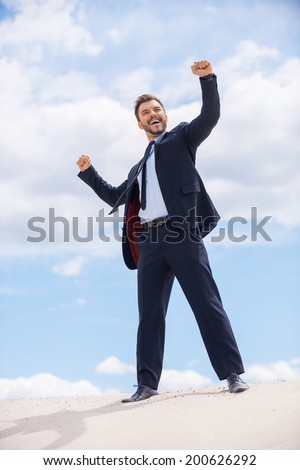 This is success! Happy young man in formalwear keeping his arms raised while standing on the top of sand dune and against blue sky  - stock photo