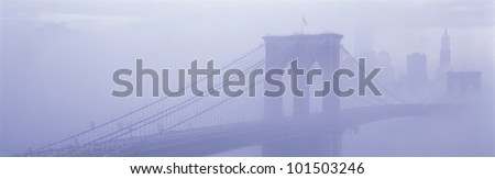 This is the Brooklyn Bridge over the East River. There is a morning fog enveloping the bridge and city. - stock photo