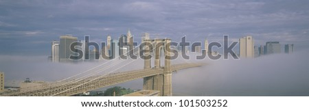 This is the Brooklyn Bridge over the East River with the Manhattan skyline without the World Trade Center behind it. There is a morning fog enveloping the bridge. - stock photo