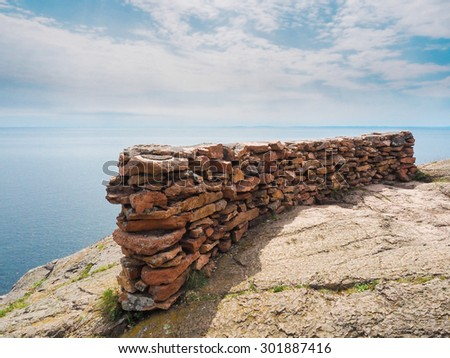 This is the edge of the cliff with rocks stacked as a barrier at Palisade Head. This is in the Lake Superior North Shore in Minnesota. - stock photo