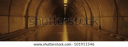 This is the interior of a tunnel. There is an orange glow from lights on the surrounding walls with a small light at the end of the tunnel. There is a road leading through the tunnel. - stock photo