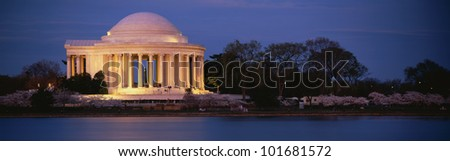 This is the Jefferson Memorial next to the Tidal Basin. Cherry blossoms are blooming on the trees surrounding it at dusk. - stock photo
