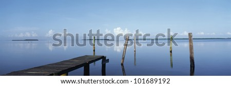 This is the morning view of Pine Island Sound. Its pier juts out from the left side with wooden pylons standing up out of the water near the shore. - stock photo