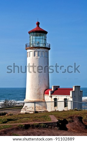 This is the North Head lighthouse off the Pacific ocean in Washington state in Pacific County, with a bright clear blue sky.  Beautiful lantern room is at the top with a red roof for details.