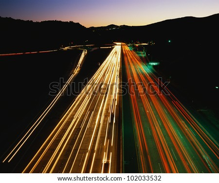 This is the San Diego Freeway also known as the 405. These are the streaked lights of the cars at night at rush hour. - stock photo