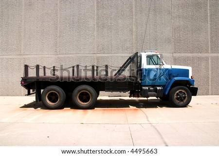 This is the side view of a flat bed straight truck with a city style day cab. - stock photo