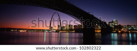 This is the St. Louis skyline and Arch at sunset. Above it is the Eads Bridge along the Mississippi River. There is a purple cast in the sunset sky. - stock photo