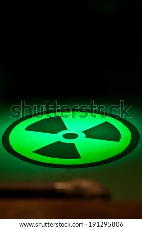 This is the symbol for the chemical radium, painted on a floor with green lights shinning on it against a black wall in vertical format. - stock photo