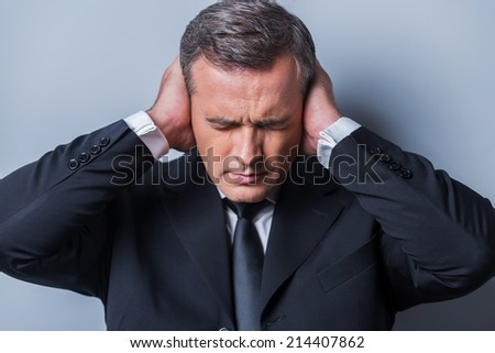 This is too loud! Frustrated mature man in formalwear holding head in hands and keeping eyes closed while standing against grey background - stock photo