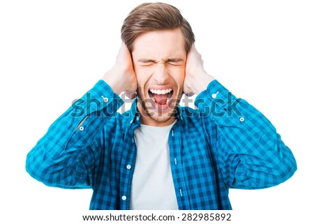 This is too loud! Frustrated young man holding head in hands and keeping eyes closed while standing against white background - stock photo