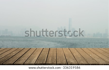 this is town of blurred blue color and wooden terrace space front and Hong Kong Sea Coast
