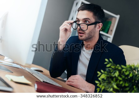 This is unbelievable! Surprised young man in smart casual wear adjusting his eyeglasses and looking at computer monitor while sitting at his working place in office - stock photo