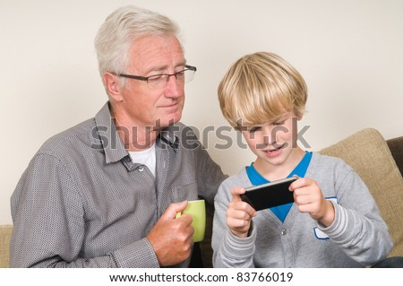 This kid learns his grandpa to use a smartphone - stock photo