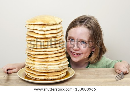 This kid's about to tackle a large stack of pancakes for breakfast