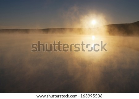 This late fall sunrise across a calm lake became almost spiritual as a calm mist rose when the sun's rays reached the water's surface. - stock photo