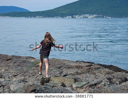 This little girl is jumping the rocks at the beach while exploring the seashore in a carefree childhood moment.