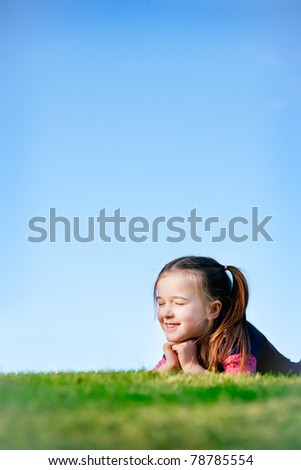 This little girl is looking dreamy or imaginative.  Whatever she's thinking about - it is making her feel happy.  She almost looks a little mischievously. - stock photo