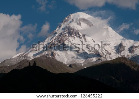 This majestic mount against the blue sky with roll clouds is  Kazbek - Caucasus, Georgia. The silhouette  of Gergeti Trinity Church is in the foreground.