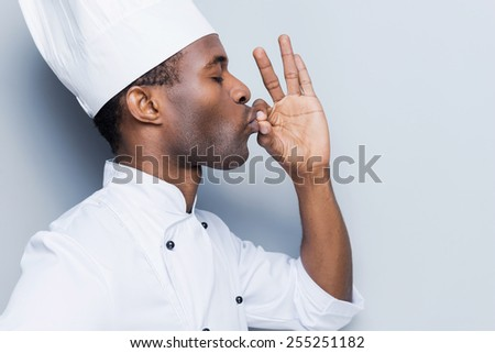 This meal is just perfect! Side view of confident young African chef in white uniform keeping eyes closed and gesturing while standing against grey background - stock photo