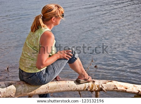 This middle aged Caucasian woman with blond hair in a pony tail, is sitting on a log and relaxing at a lake.  She is enjoying a stress free, life moment, full body side view. - stock photo