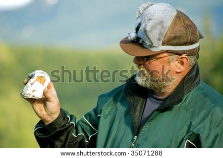 This middle aged man is wearing a goofy koala bear hat while showing off a unique rock he found in the mountains.
