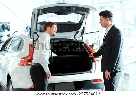 This model is popular. Rear view of a young handsome salesman speaking with his satisfied client in car dealership while standing at new car