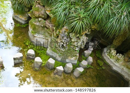 this narrow winding footpath in the lake leads to the cave. Quinta da Regaleira, Sintra, Portugal - stock photo