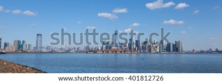 This panorama contains views of Jersey City and Manhattan, from Liberty State Park. Goldman Sachs Tower, 432 Park, Empire State Building, Freedom Tower, Ellis Island, and Brooklyn Bridge are seen. - stock photo