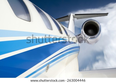 This photo illustration of a business jet is created from a unique in-flight perspective with slight motion or zoom blur added, beautiful clouds and deep blue sky. All components my own.  - stock photo