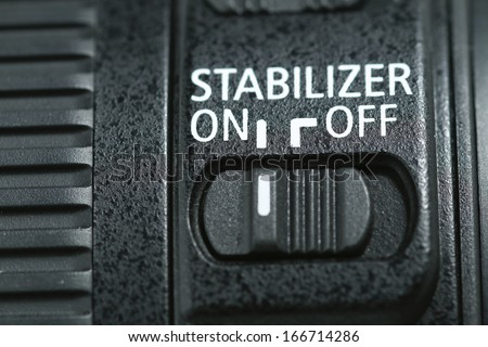 "This photo shows a closeup to a lens stabilizer button on the ""On"" position ."