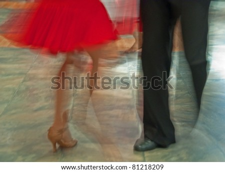 This photo shows a couple ballroom dancing from the waist down with the picture full of motion.  Ladies' red skirt is swinging to the movement of the dance and music.