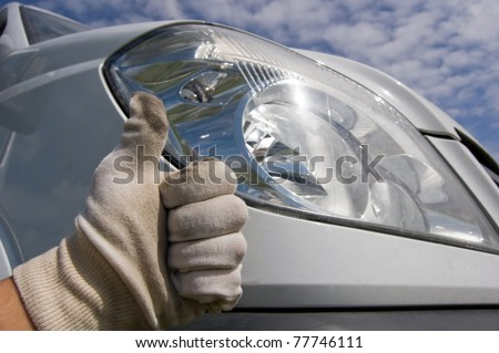This photo shows a mechanic using white gloves and doing an ok sign refering to a car status, wich has been reviewed.